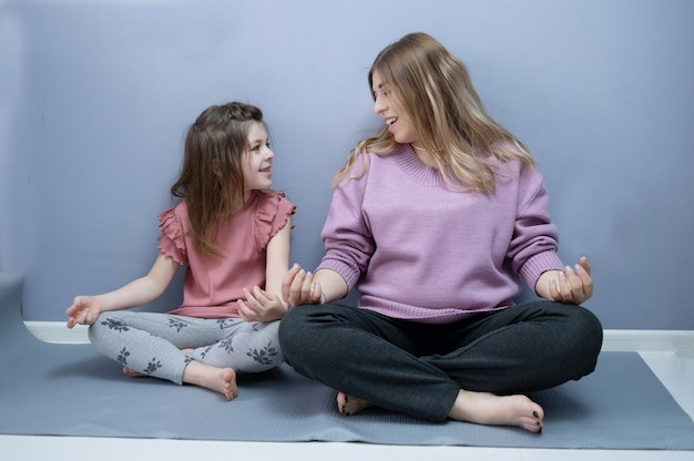 Kaukasisch gelukkig preschool meisje met blonde zwangere moeder maakt yoga thuis samen