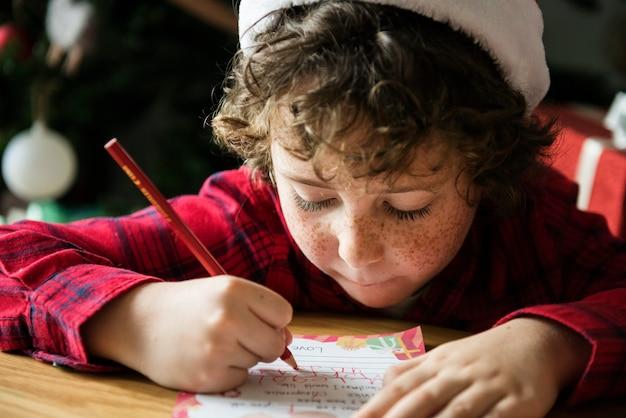 Kaukasisch jong geitje dat een wenskaart van kerstmis schrijft