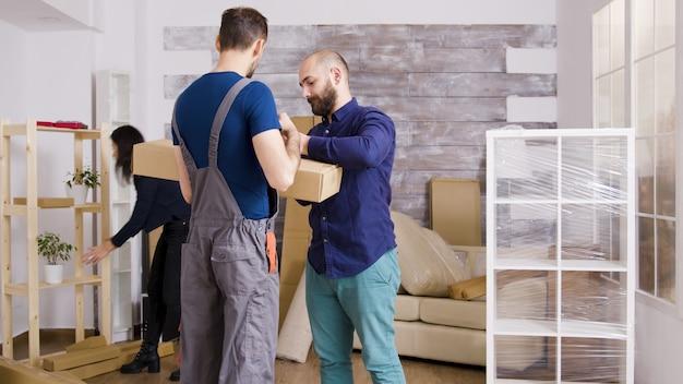 Kaukasisch jong gezin verhuizen naar nieuw appartement. vriend ondertekent voor het ontvangen van dozen van de bezorgservice.