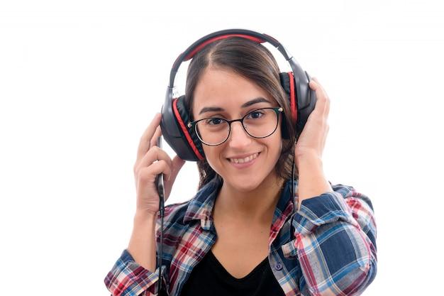 Kaukasisch jong meisje dat aan muziek met grote hoofdtelefoons luistert die op witte achtergrond wordt geïsoleerd