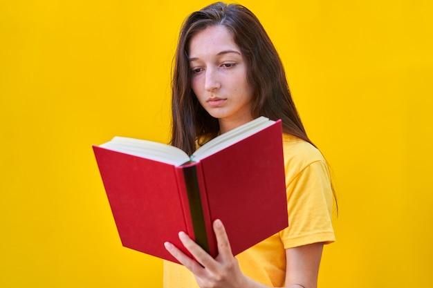 Kaukasisch jong meisje dat met lang donkerbruin haar een rood boek leest