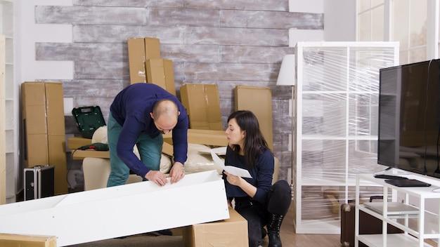 Kaukasisch jong stel in nieuw appartement dat meubels monteert en instructies leest. vriend die schroevendraaier gebruikt. inzoomen opname