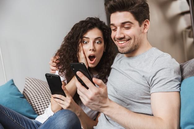 Kaukasisch jong stel man en vrouw die thuis op de bank zitten en samen smartphone gebruiken