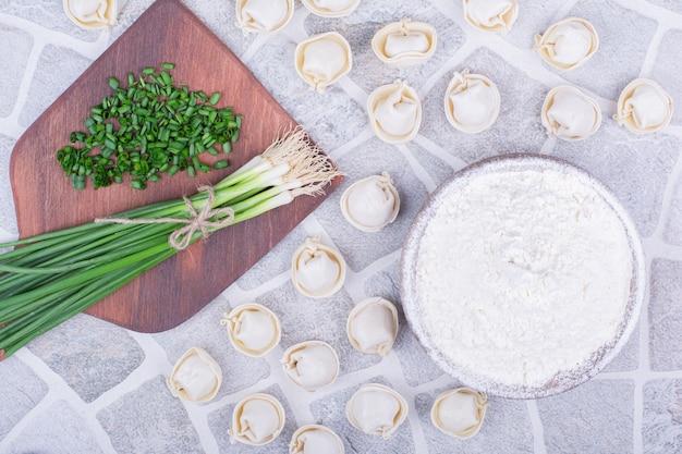 Kaukasisch khinkali-deeg op een houten bord met groene uien