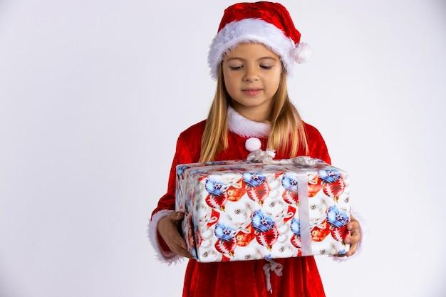 Kaukasisch kind in santa rode hoed kerstcadeau in de hand te houden en naar hem te kijken. geïsoleerd op