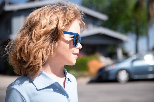 Kaukasisch kind in zonnebril, portret close-up. kinderen buiten huis, in de buurt van huis.
