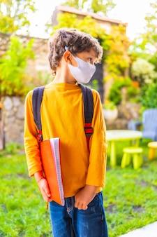 Kaukasisch kind met gezichtsmasker klaar voor terug naar school. nieuwe normaliteit, sociale afstand, coronavirus-pandemie, covid-19. oranje t-shirt, rugzak en een notitieblok in de hand