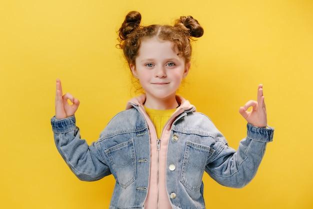 Kaukasisch klein meisje dat goed gebaar toont met beide handen geïsoleerd op gele achtergrond