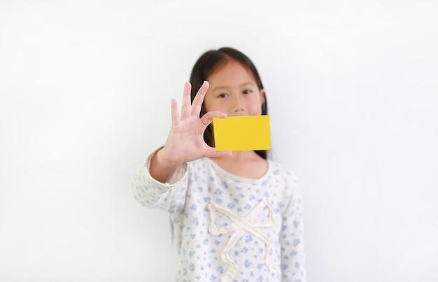 Kaukasisch klein meisje dat lege gele kaart op witte achtergrond toont. focus op kaart in zijn hand