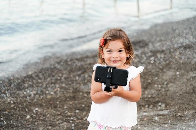 Kaukasisch klein meisje met selfiestick aan de kust. foto maken, vlog opnemen, videogesprek