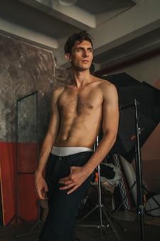 Kaukasisch knap krullend mannelijk model poseren op de foto met bliksemapparatuur.