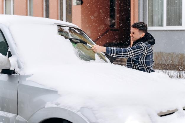 Kaukasisch mannetje dat met een speciale borstel staat en sneeuw uit het raam verwijdert. man schept en verwijdert sneeuw uit zijn auto tijdens een sneeuwstorm