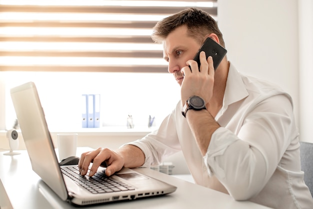 Kaukasisch mannetje dat van huisbureau werkt en op de telefoon spreekt