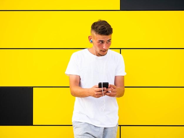 Kaukasisch mannetje dat zijn telefoon op gele muur gebruikt