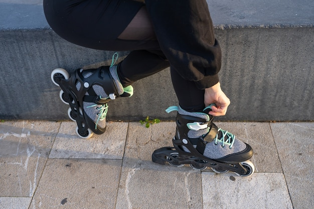 Kaukasisch meisje bindt haar schaatsen vast terwijl ze op een bank zit