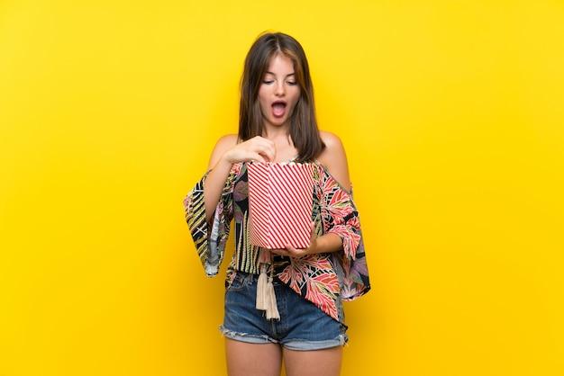 Kaukasisch meisje dat in kleurrijke kleding popcorns eet