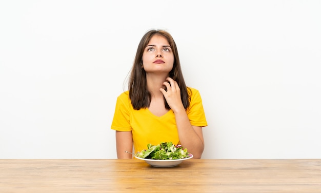 Kaukasisch meisje dat met salade een idee denkt