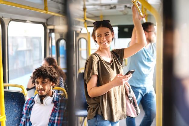 Kaukasisch meisje die in openbare bus drijven en slimme telefoon met behulp van voor het lezen van of het schrijven van bericht.