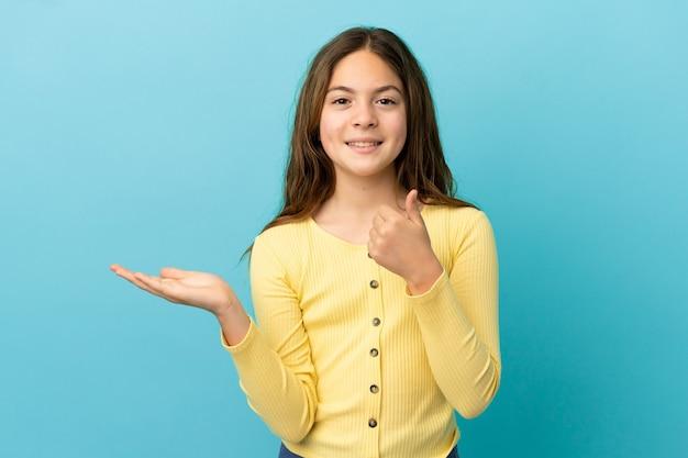 Kaukasisch meisje geïsoleerd op blauwe achtergrond met copyspace denkbeeldig op de palm om een advertentie in te voegen en met duimen omhoog