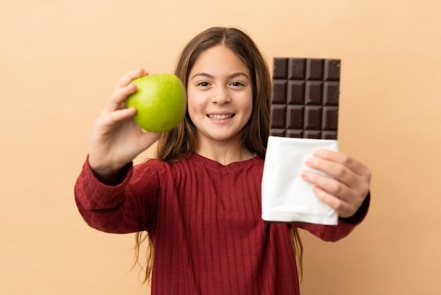 Kaukasisch meisje geïsoleerd op een beige achtergrond met een chocoladetablet in de ene hand en een appel in de andere
