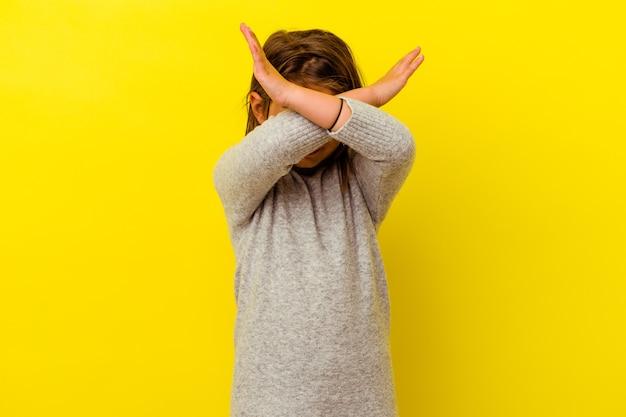 Kaukasisch meisje geïsoleerd op een gele achtergrond die twee armen gekruist houdt, ontkenningsconcept.