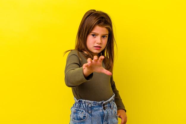 Kaukasisch meisje geïsoleerd op een gele achtergrond met klauwen die een kat imiteren, agressief gebaar.