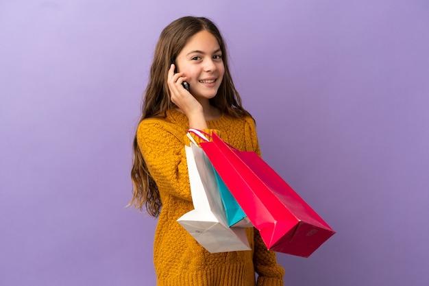 Kaukasisch meisje geïsoleerd op een paarse achtergrond met boodschappentassen en een vriend bellen met haar mobiele telefoon