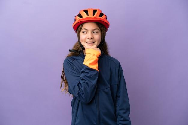 Kaukasisch meisje geïsoleerd op een paarse achtergrond op zoek naar de kant en glimlachend