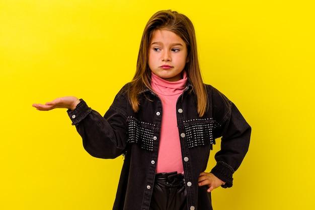 Kaukasisch meisje geïsoleerd op gele achtergrond twijfelend en schouderophalend in vragend gebaar.