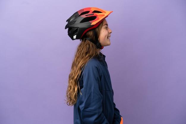 Kaukasisch meisje geïsoleerd op paarse achtergrond lachen in zijpositie