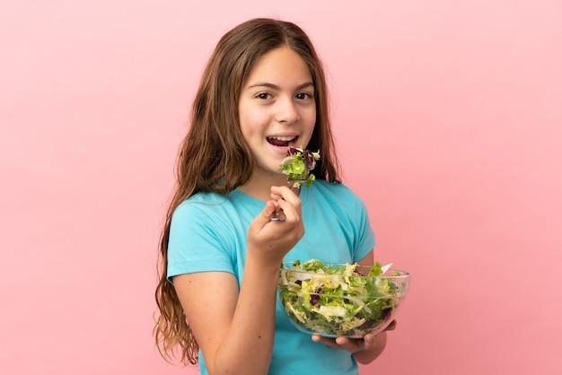 Kaukasisch meisje geïsoleerd op roze achtergrond met een kom salade met gelukkige uitdrukking