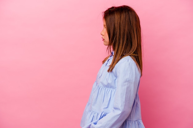Kaukasisch meisje geïsoleerd op roze achtergrond staren naar links, zijwaarts poseren.
