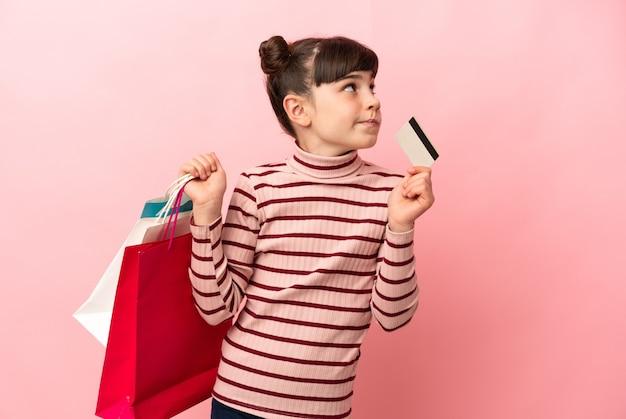 Kaukasisch meisje geïsoleerd op roze bedrijf boodschappentassen en een creditcard en denken