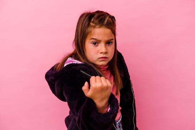 Kaukasisch meisje geïsoleerd op roze vuist tonen aan camera, agressieve gezichtsuitdrukking.