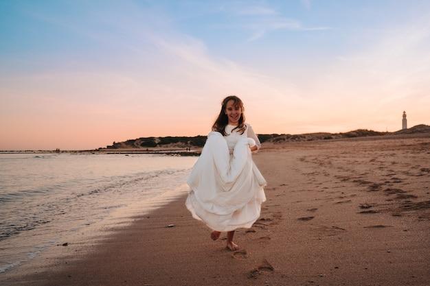 Kaukasisch meisje gekleed in communie in een zonsondergang op het strand terwijl ze gelukkig is