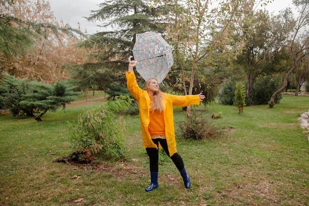 Kaukasisch meisje in een gele regenjas die buiten loopt op de regenachtige dag in de herfst mensen in de herfst