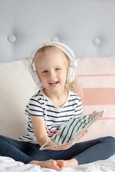 Kaukasisch meisje in hoofdtelefoon kijken tablet in bed, interieur, moderne apparaattechnologieën scandinavische stijl