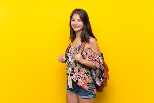Kaukasisch meisje in kleurrijke kleding dat op geel met rugzak wordt geïsoleerd