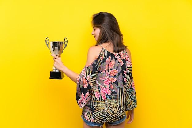 Kaukasisch meisje in kleurrijke kleding over geïsoleerde gele muur die een trofee houdt