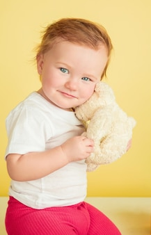 Kaukasisch meisje, kinderen geïsoleerd op gele studio achtergrond. portret van schattig en schattig kind, baby spelen en glimlachen.