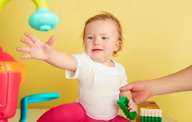 Kaukasisch meisje, kinderen geïsoleerd op gele studio achtergrond. portret van schattig en schattig kind, baby spelen en lachen.