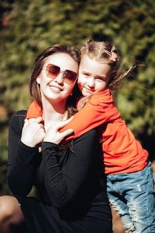Kaukasisch meisje knuffelt haar mooie moeder in het zomerpark