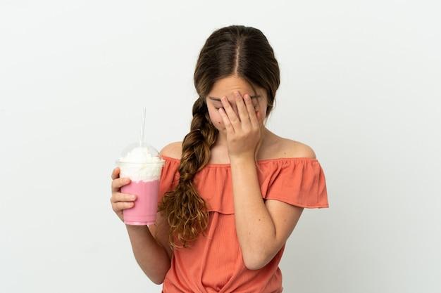 Kaukasisch meisje met aardbeienmilkshake geïsoleerd op een witte achtergrond met vermoeide en zieke expressie
