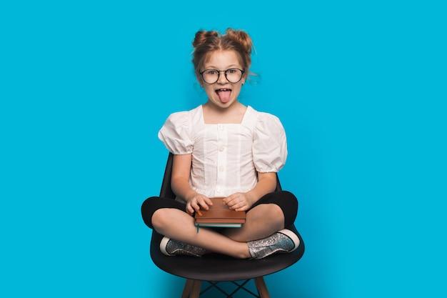 Kaukasisch meisje met bril glimlacht en toont tong terwijl ze in een fauteuil zit met een boek op een blauwe studiomuur