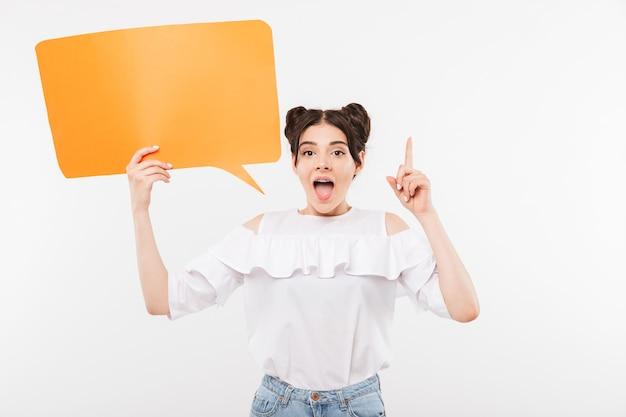 Kaukasisch meisje met dubbele broodjes kapsel met lege bel voor copyspace tekst en wijzende vinger naar boven, geïsoleerd op wit