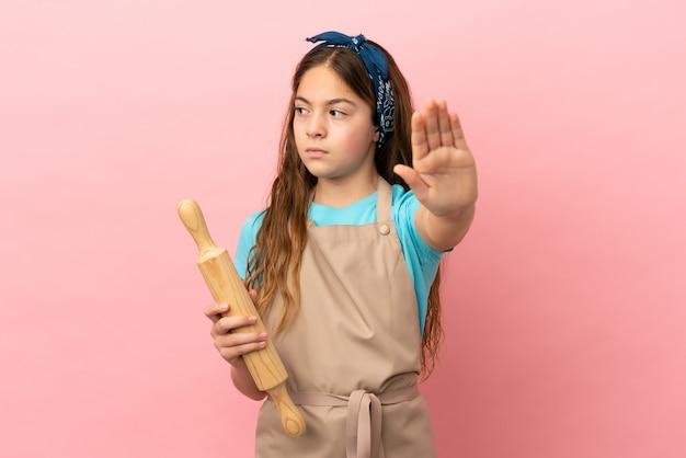 Kaukasisch meisje met een deegroller geïsoleerd op een roze achtergrond die een stopgebaar maakt en teleurgesteld is