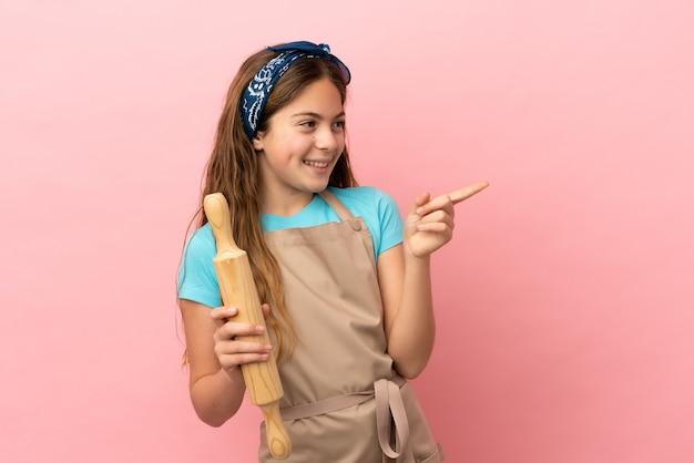 Kaukasisch meisje met een deegroller geïsoleerd op een roze achtergrond die met de vinger naar de zijkant wijst en een product presenteert