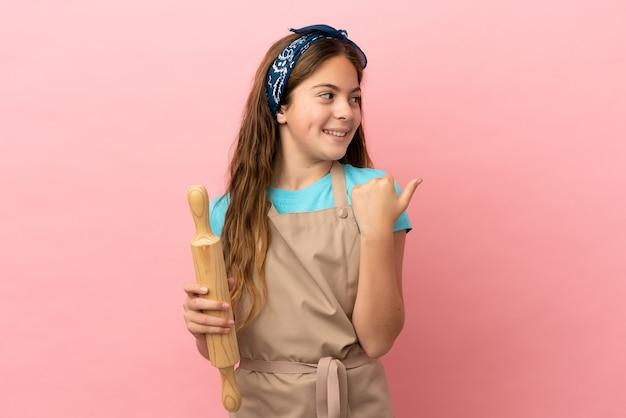 Kaukasisch meisje met een deegroller geïsoleerd op een roze achtergrond die naar de zijkant wijst om een product te presenteren
