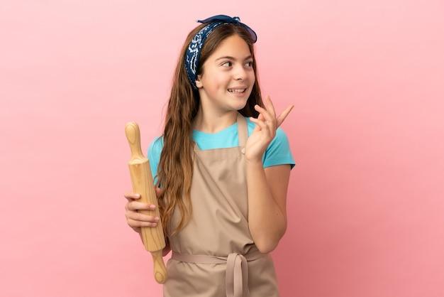Kaukasisch meisje met een deegroller geïsoleerd op een roze achtergrond met de bedoeling de oplossing te realiseren terwijl ze een vinger optilt