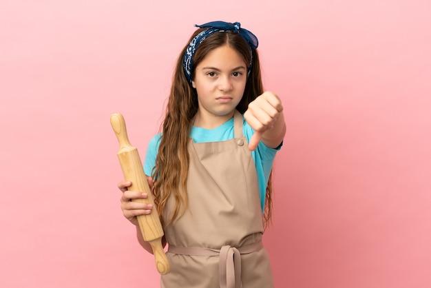 Kaukasisch meisje met een deegroller geïsoleerd op een roze achtergrond met duim omlaag met negatieve uitdrukking